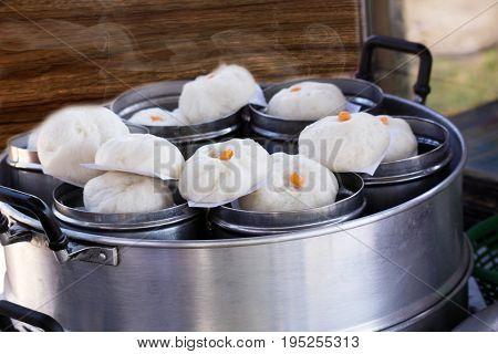 Chinese dumplings(steamed stuff bun) being steamed in steam box.