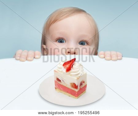 Picture of a little baby who is looking for a piece of strawberry cake