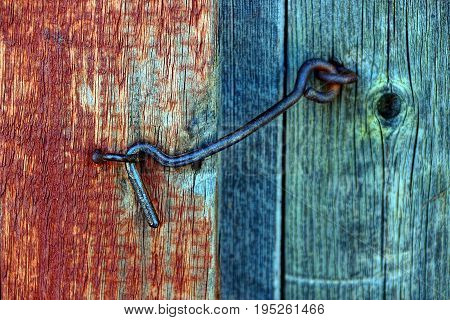 Iron old hook latch in a loop on an old wooden door