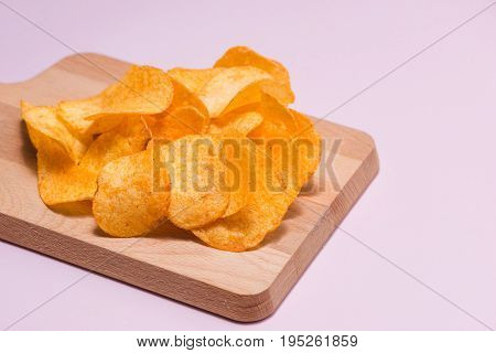 Salty crispy potato chips on cutting board.