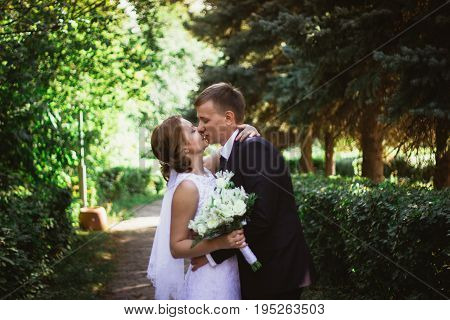 couple bride and groom on a park background.
