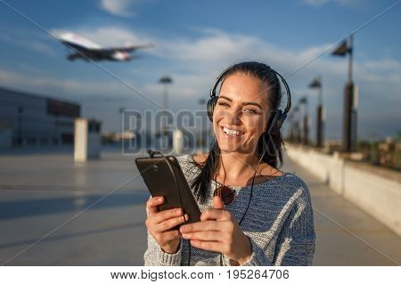 Happy young woman with headphones buying air tickets by tablet