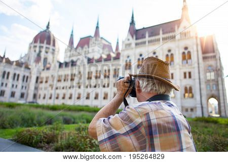 Pensioner tourist capturing Hungarian Parliament in sunset Hungary