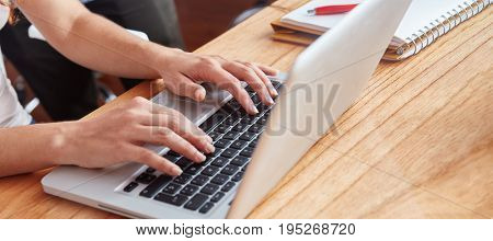 Programmer with laptop computer typing and working