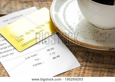 credit card for paying, cup of coffee and check on cafe wooden desk background