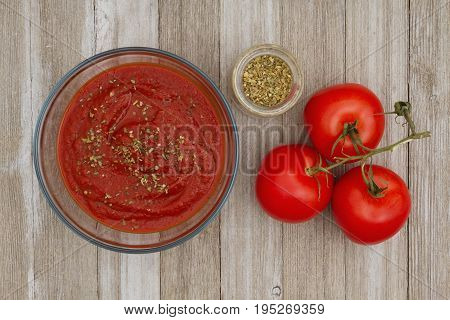 Tomato sauce in clear bowl with oregano spice and red vine ripe tomatoes on weathered wood background