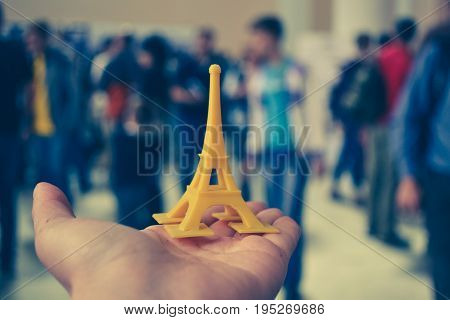 The model is yellow printed on a 3d printer on hand close-up. On the back of a blurry plan - people. Progressive modern additive technology. Copy spase