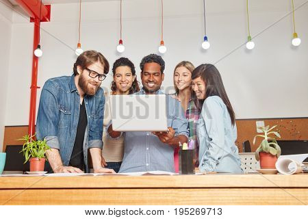 Young creative founder in successful startup team holding laptop
