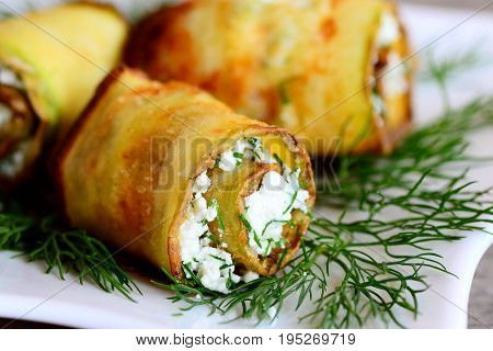 Fried cheese stuffed zucchini. Homemade fried zucchini rolls stuffed with cottage cheese and finely chopped dill on a white plate. Closeup