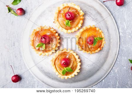 Apple Caramel Little Tarts On Grey Background. French Tatin With Paradise Apple. Top View.
