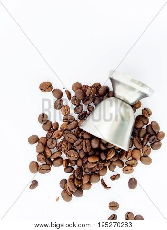 Coffee beans and small metal cup on white background top view