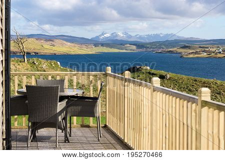 Terrace with table and chairs. Beautiful view over blue water and mountains on Isle of Skye, Scotland.