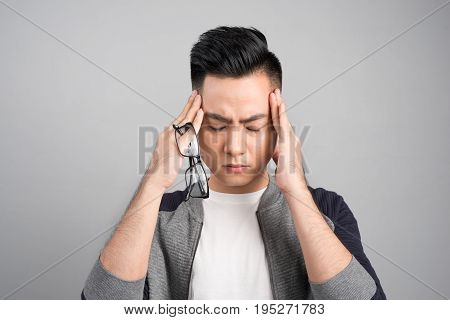 Frustrated business asian man with a headache - isolated over gray