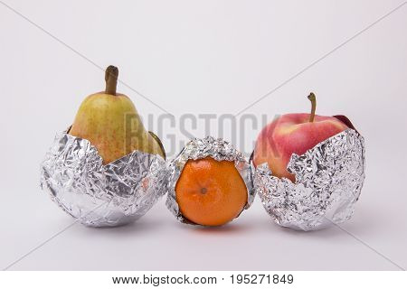 Juicy mandarin orange yellow pear and red apple wrapped in foil on a white background