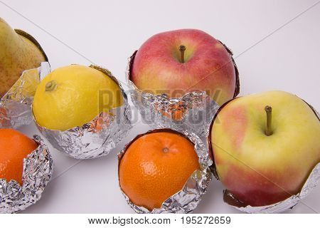 Juicy fruit yellow pear red apple lemon and orange tangerines wrapped in foil on a white background