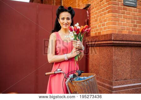 Beautiful Women Walking In The City With Bicycle And Flowers.