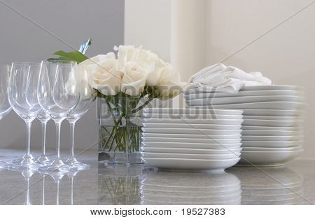 plates, glasses & roses on counter for dining