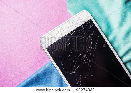 Crushed mobile phone on a multi-colored background