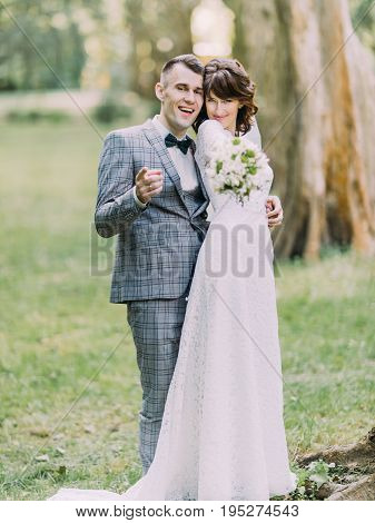 The funny portrait of the cheerful newlyweds spending time in the park