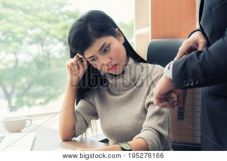 Angry business manager pointing his watch to subordinate businesswoman working missed deadline. Boss and worker at work having conflict.
