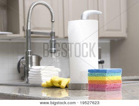 rainbow sponges, paper towels, gloves in modern kitchen for housework - focus on front sponge