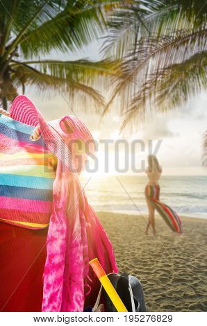 Beach bag on the beach at sunset with woman standing on background