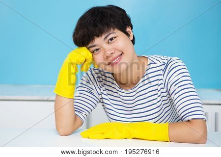 Closeup portrait of smiling young pretty Asian woman looking at camera, wearing protective gloves and sitting at table in kitchen