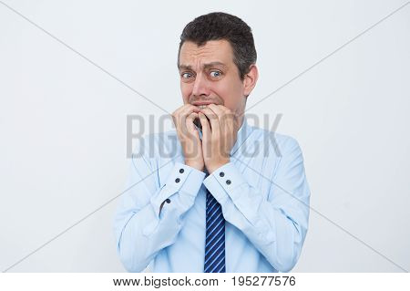 Anexious young businessman chewing fingernails when worrying. Emotional male manager before meeting. Nervous entrepreneur looking at camera. Stress concept