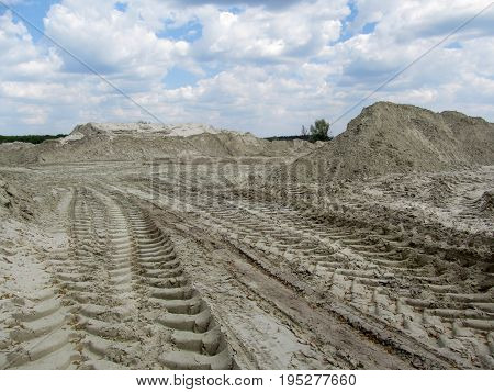 Sandy quarry with prints of tires of the tippers and a beautiful sky in the clouds above it. Heaps of white industrial sand and gentle blue sky above them