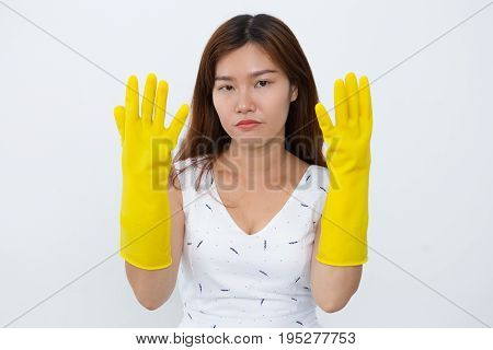 Tired young Asian woman showing hands in cleaner gloves. Upset housewife exhausted cleaning. She looking at camera. Servant concept