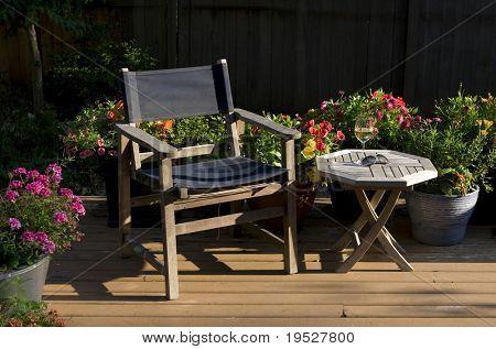 summer evening relaxation in the garden - wine, deck chair, & sunlit flowers