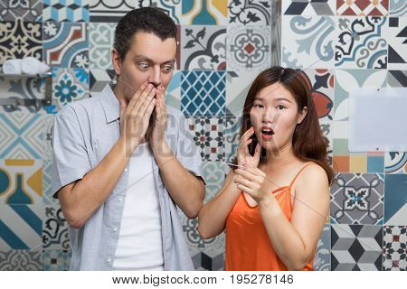 Shocked young multiethnic couple knowing about pregnancy. Confused partners standing opposite colorful wall and amazed test result. Unexpected pregnancy concept