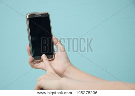 Bangkok Thailand July 8 2017 : Woman held android smart phone Samsung galaxy S7 Edge on blue concrete background.