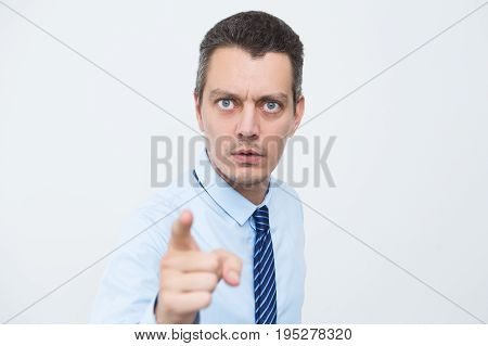 Portrait of worried businessman pointing with index finger to camera. Scared male manager looking at camera. He choosing you. Fear or reprimand concept