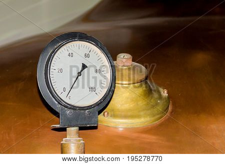 Industrial background pressure gauge to determine the pressure opposite the copper color tank with a beer factory valve