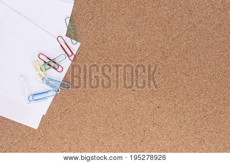 Paper with paper clips on a wooden background with copy space