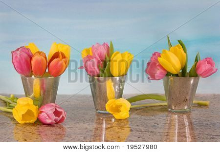 tulips in vases on blue watercolor background with granite countertop
