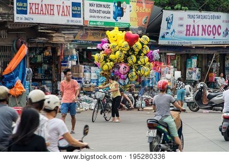 Hanoi, Vietnam - August 16, 2015: a young Vienamese helium balloon saleswoman on a bicycle, selling Despicable Me balloons in the Old Quarter.