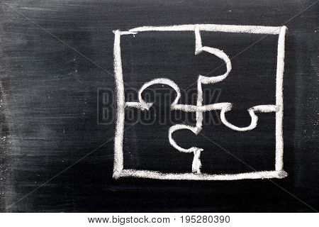Chalk hand drawing as puzzle shape on black board background