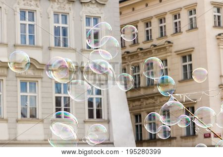 Large bright shiny soap bubbles fly against the background of a beige white house
