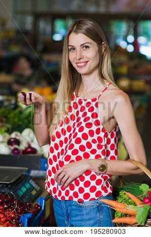 Portrait of a girl with a basket of vegetables. Beautiful blond young girl with a full basket of fruits and vegetables in a vegetable market. Look at the camera. Girl posing with a full basket of vegetables.