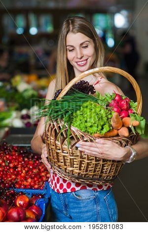 Portrait of a girl with a basket of vegetables. Beautiful blond young girl with a full basket of fruits and vegetables in a vegetable market