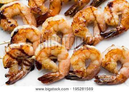 tasty spiced shrimp skewers on a barbecue.