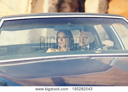 Elegant gorgeous bride and handsome groom embracing in stylish car. Luxury wedding couple in retro style.
