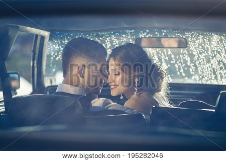 Portrait of happy newlywed couple in car on sunset after rain