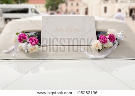White wedding limousine decorated with red and white flowers. Inscription in english 'Just Married'