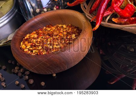 Red chili peppers and wooden bowl of chili flakes on black background with reflection
