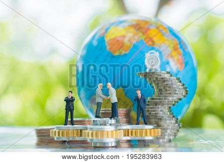 Miniature businessman handshaking on the fidget spinner with globe and growing stacks of coins background using as commitment agreement investment and partnership business concept.