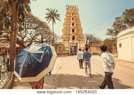 MYSORE, INDIA - FEB 17, 2017: Hindu people walking to traditional Indian gopuram - tower of tample gate on February 17, 2017. With population 900000 Mysore is the cultural capital of Karnataka