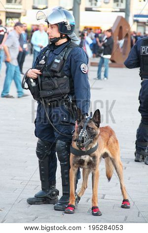 MARSEILLE, FRANCE - JUNE 21, 2016: French policeman with the german shepherd dog patrolling the street in Marseille